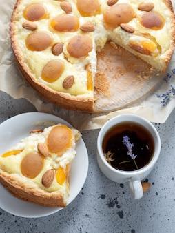 Hausgemachter kuchen mit mandeln und aprikosen. eine tasse kräutertee mit lavendel.