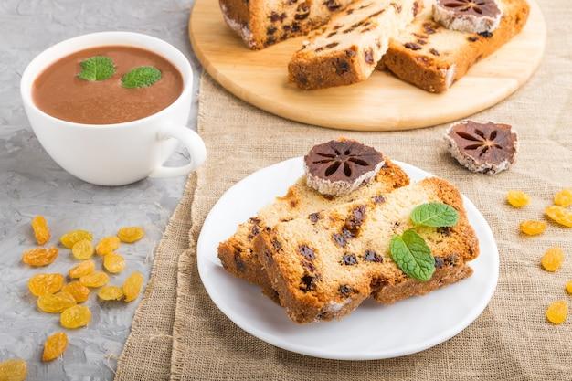 Hausgemachter kuchen mit rosinen, getrockneter kaki und einer tasse heißer schokolade