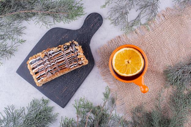 Hausgemachter kuchen und eine tasse tee auf marmoroberfläche mit tannenzweig. foto in hoher qualität