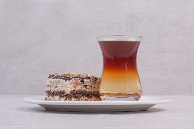 Hausgemachter kuchen und tasse tee auf weißem teller.
