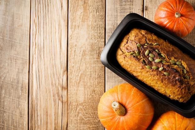 Hausgemachter kürbis mit samenkuchen auf hölzernem hintergrund. thanksgiving und herbstthema