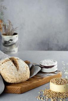 Hausgemachter laib aus frisch gebackenem grünem buchweizenbrot liegt auf einem hölzernen küchenbrett mit grauer leinenserviette. harmloses, wellness, glutenfreies gesundes backen für veganer und vegetarier.alternatives brot