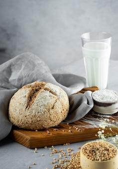 Hausgemachter laib aus frisch gebackenem grünem buchweizenbrot und bio-buchweizenmilch. serviette aus holz, leinen. harmloses, wellness, glutenfreies gesundes backen für veganer. alternatives brot und vegetarische milch