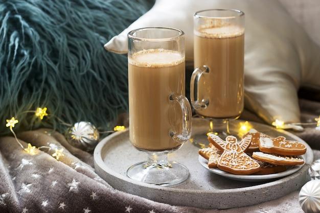 Hausgemachter latte in glastassen, serviert mit lebkuchen auf plaid, kissen und girlanden.