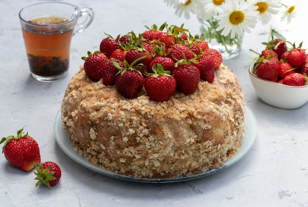 Hausgemachter lebkuchenkuchen garniert mit frischen erdbeeren auf hellgrauem hintergrund. sommerstillleben im freien. nahansicht