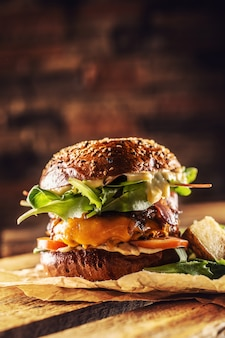 Hausgemachter leckerer burger mit speck-zwiebel-käse und salat auf holzkiste.