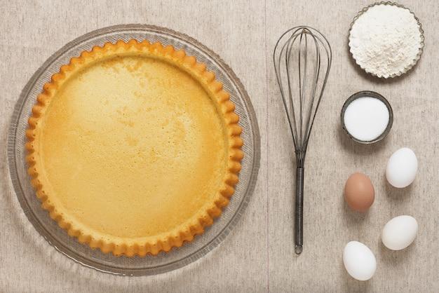 Hausgemachter leerer flan-kuchen mit rezeptzutaten und küchenutensilien auf vintage-leinentischdecke. draufsicht.