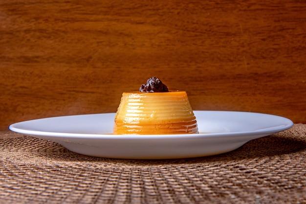 Hausgemachter milchpudding mit karamellcreme. traditionelles brasilianisches dessert auf einem teller auf hölzernem hintergrund.