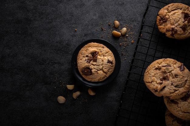 Hausgemachter milchschokoladen-macadamia-cookie auf schwarzem hintergrund. ansicht von oben.