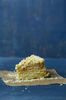 Hausgemachter napoleon-kuchen mit sahne auf grauem hintergrund.