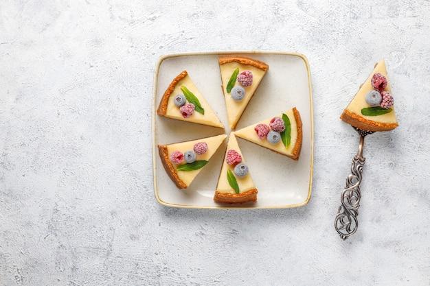 Hausgemachter new yorker käsekuchen mit gefrorenen beeren und minze, gesundes bio-dessert, draufsicht
