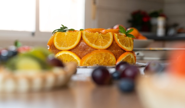 Hausgemachter orangenkuchen mit geschnittenen orangen in einer küche