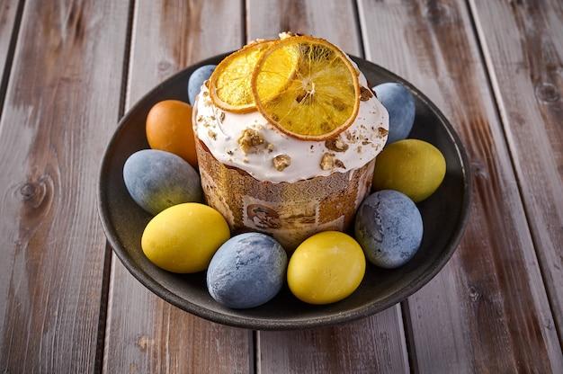Hausgemachter osterkuchen und bunt bemalte eier auf schwarzem teller