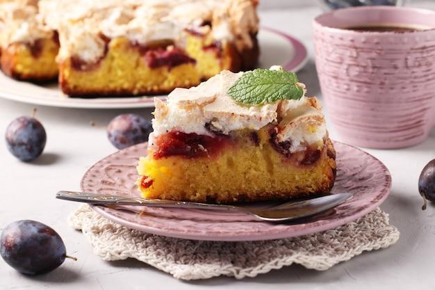 Hausgemachter pflaumenkuchen bedeckt mit süßem baiser auf einem teller auf hellem hintergrund. nahaufnahme.