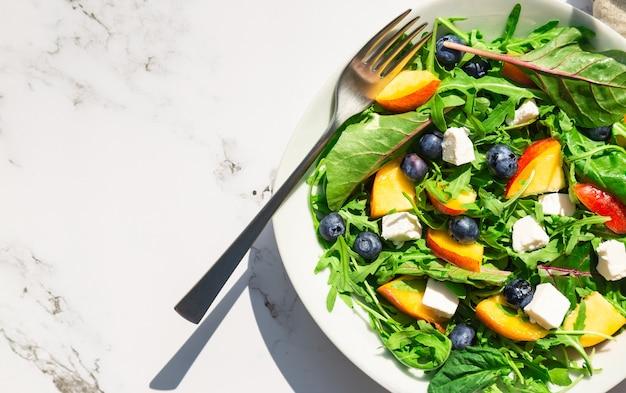 Hausgemachter salat mit nektarinen blaubeeren rucola und feta auf weißem marmorhintergrund