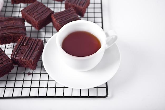 Hausgemachter schokoladen-brownie und eine tasse kaffee auf dem träger