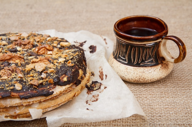 Hausgemachter schokoladen-puffkuchen und braune tontasse kaffee auf dem sack.
