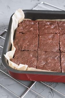 Hausgemachter schokoladenbrownie in einer backform in quadratische stücke geschnitten
