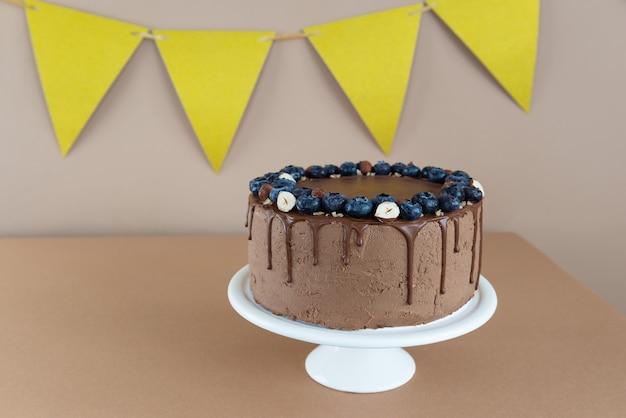 Hausgemachter schokoladenkuchen mit blaubeeren und nüssen auf braunem hintergrund mit gelber weihnachtsdeko
