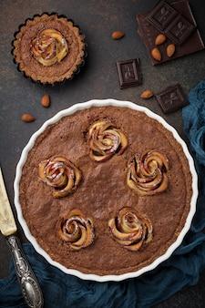 Hausgemachter schokoladenkuchen mit frangipane und apfelblüten auf dunklem beton