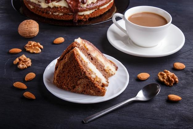 Hausgemachter schokoladenkuchen mit milchcreme, karamell und mandeln. tasse kaffee.