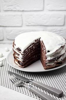 Hausgemachter schokoladenkuchen mit sahne. ein stück kuchen wird abgeschnitten