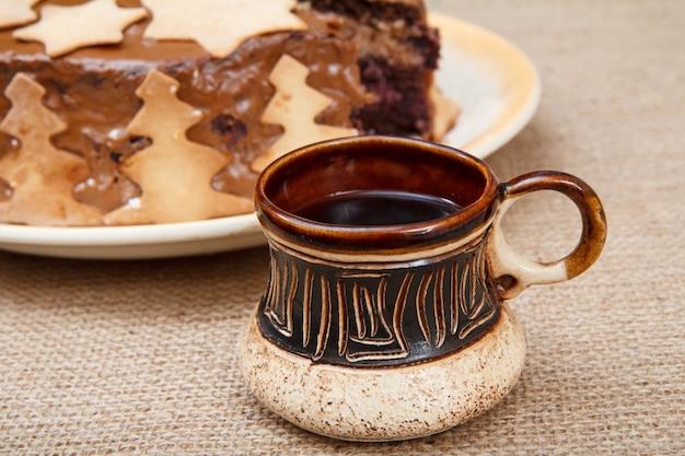 Hausgemachter schokoladenkuchen mit weihnachtsschmuck und tontasse schwarzen kaffees auf dem sack.