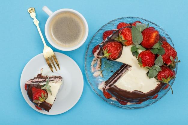 Hausgemachter schokoladenkuchen verziert mit frischen erdbeeren und minzblättern auf glasplatte, stück kuchen mit gabel auf weißem teller und tasse kaffee auf blauem hintergrund color