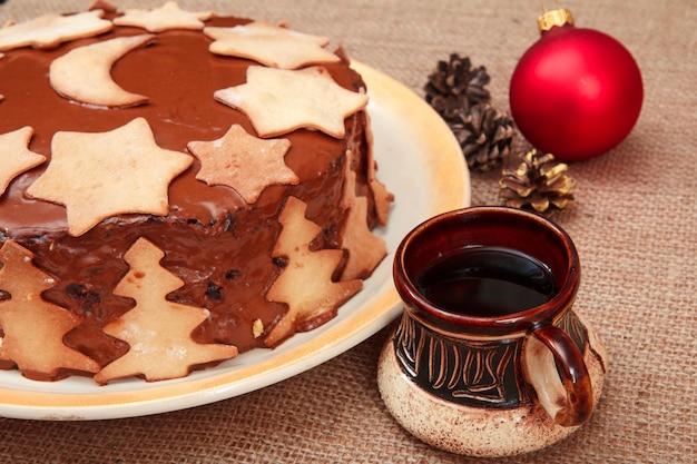 Hausgemachter schokoladenkuchen verziert mit weihnachtsschmuck, tasse kaffee, zapfen und spielzeugball auf dem sack.