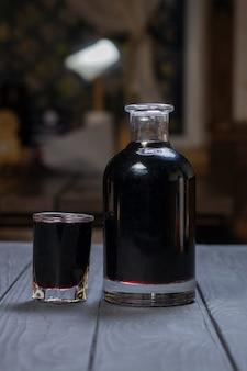 Hausgemachter schwarzer apfelbeerwein oder -likör auf schwarzer holzoberfläche