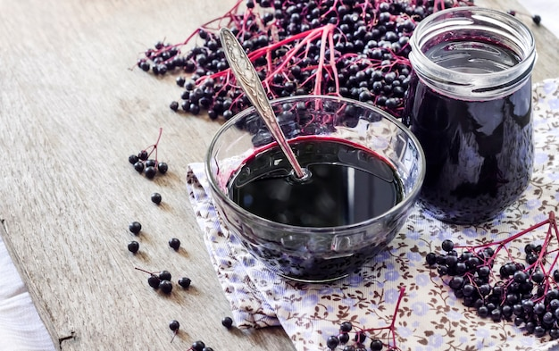Hausgemachter schwarzer holundersirup in glasschüssel und glas