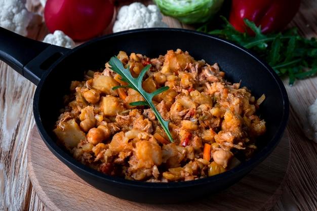 Hausgemachter schweineeintopf mit gemüse, kartoffeln, zwiebeln, karotten, blumenkohl, pfeffer mit tomatensauce, knoblauch und kräutern in einer bratschale auf holztisch.