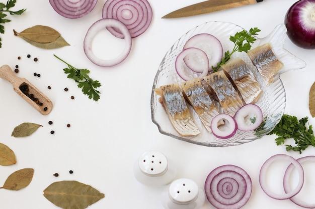 Hausgemachter snack aus gesalzenem hering mit roten zwiebeln und senf auf weißem hintergrund, ansicht von oben