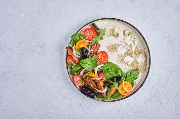 Hausgemachter styling-salat mit gebratenen auberginen, tomaten, rucola, spinat, salat und sauce auf einem keramikteller