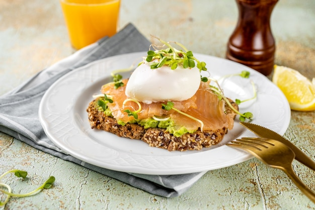 Hausgemachter toast mit avocadopüree, lachs, pochiertem ei
