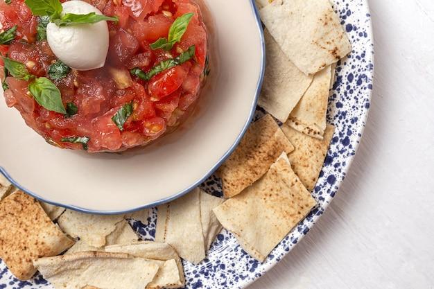 Hausgemachter tomaten-carpaccio-salat mit mozzarella, olivenöl und basilikum mit arabischem brot