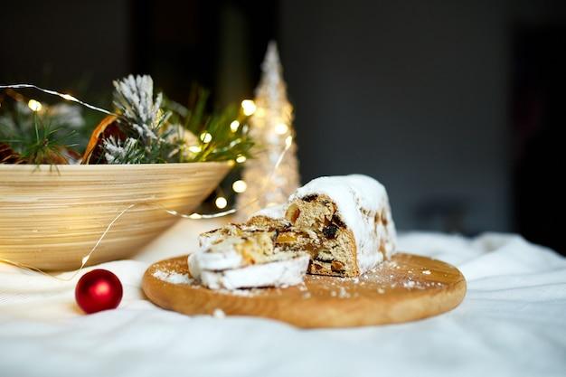 Hausgemachter traditioneller marzipan-weihnachtsstollen auf weißem hintergrund, mit weihnachtsbeleuchtung und dekorationen