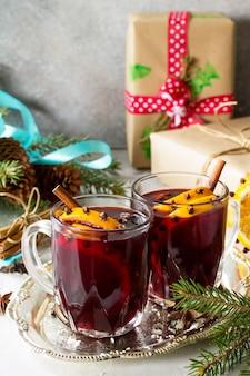 Hausgemachter weihnachtscocktail glühwein rotwein mit zimtstangen orangen textfreiraum