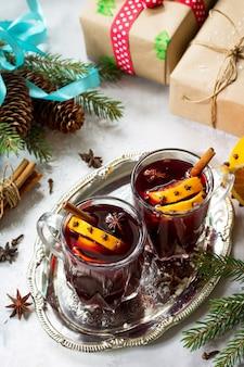 Hausgemachter weihnachtscocktail glühwein rotwein mit zimtstangen und orangen