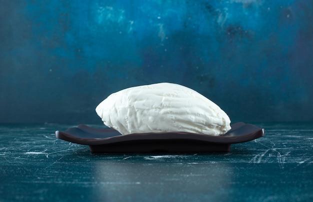 Hausgemachter weißkäse auf einem schwarzen brett. foto in hoher qualität