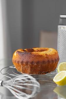 Hausgemachter zitronenkuchen auf dem grill mit einer schneebesenreibe und zitronen. kochrezept