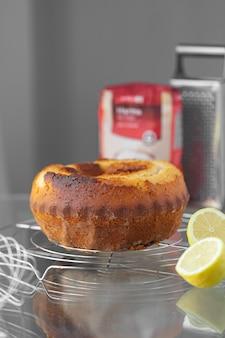 Hausgemachter zitronenkuchen auf einem grill mit einem schneebesen, geriebenem mehl und zitronen. kochrezept
