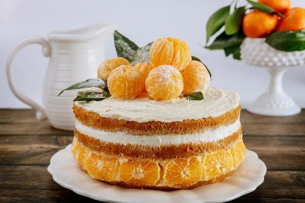 Hausgemachter zitruskuchen mit frischen mandarinen dekoriert. weihnachtskuchen.