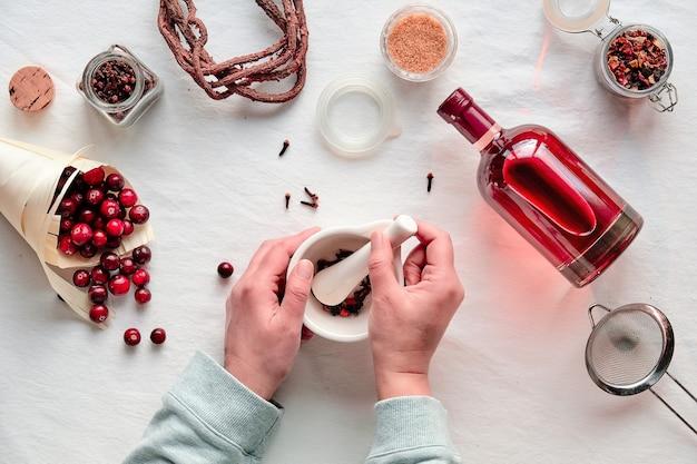Hausgemachtes alkoholgetränk. cranberry tinktur mit beeren, hände zerdrücken gewürze in mörser flach legen