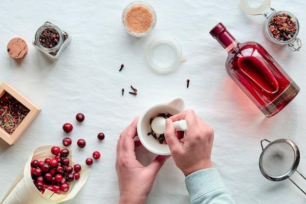 Hausgemachtes alkoholgetränk. cranberry-tinktur mit beeren, hände zerquetschen gewürze in der mörtel-draufsicht