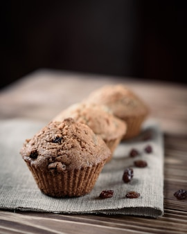 Hausgemachtes backen: cupcakes mit rosinenbonbons auf leinentuch auf einem hölzernen hintergrund.