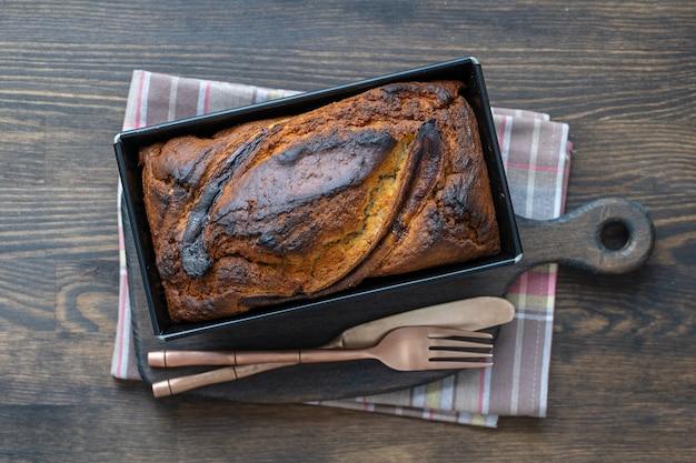 Hausgemachtes bananenbrot mit zimt auf einem holztisch, nahaufnahme, draufsicht. bananenbrot, frisch aus dem ofen auf holztisch gebacken, vintage rustikalen stillleben-stil. konzept der bäckerei