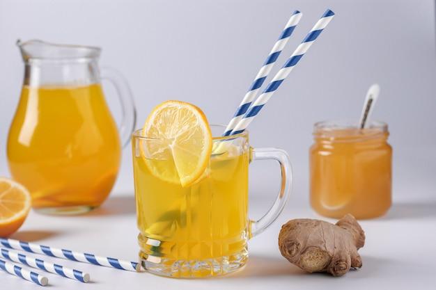 Hausgemachtes belebendes getränk mit zitrone, ingwer, honig und kurkuma auf einer weißen oberfläche, horizontale ausrichtung