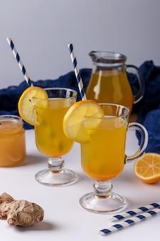 Hausgemachtes belebendes getränk mit zitrone, ingwer, honig und kurkuma auf einer weißen oberfläche, vertikale ausrichtung