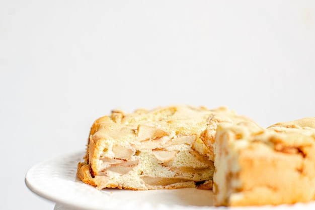 Hausgemachtes bio-apfelkuchen-dessert charlotte. cobbler apple pie auf weißem teller und weißem hintergrund